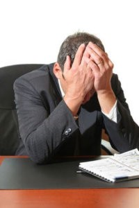 image of a frustrated business man hold his head in his hands.