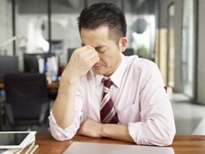 businessman looking tired and frustrated in office.